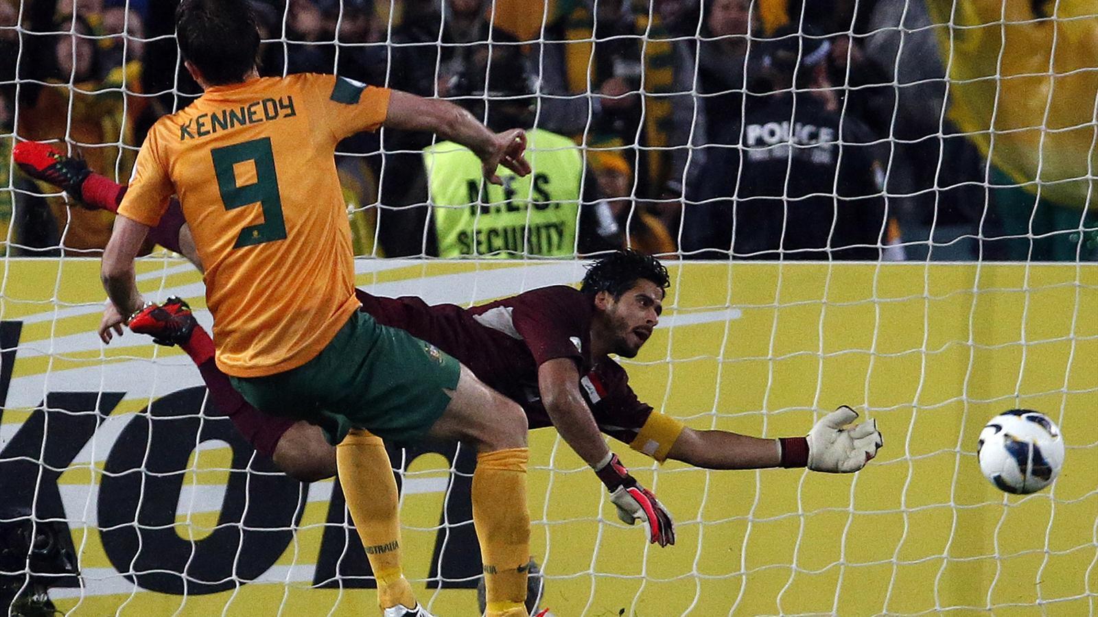 Josh kennedy l scores a goal as iraq s goalkeeper noor sabri dives