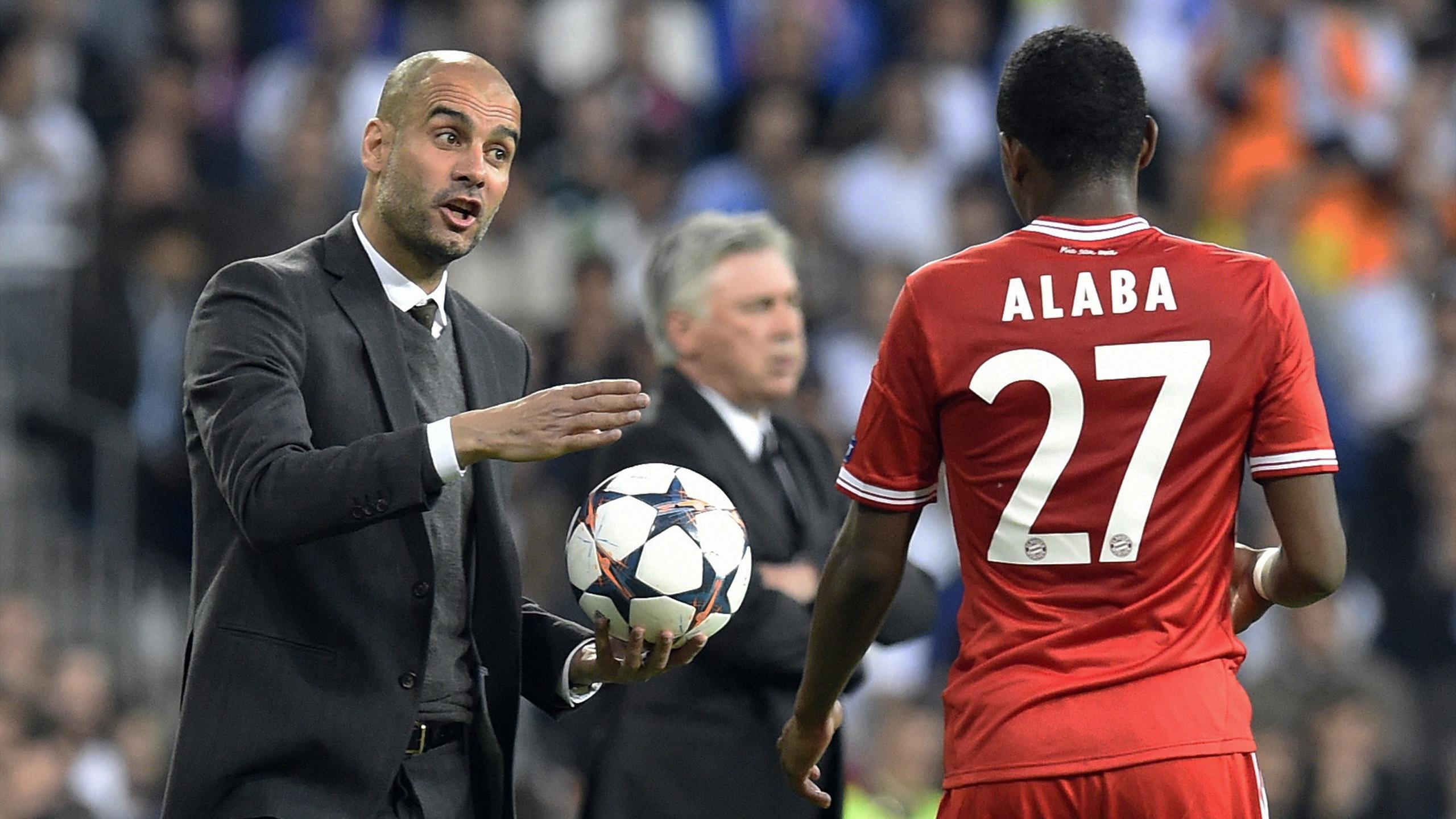 Bayern Munich's Spanish head coach Pep Guardiola (L) gives instructions to Bayern Munich's Austrian midfielder David Alaba