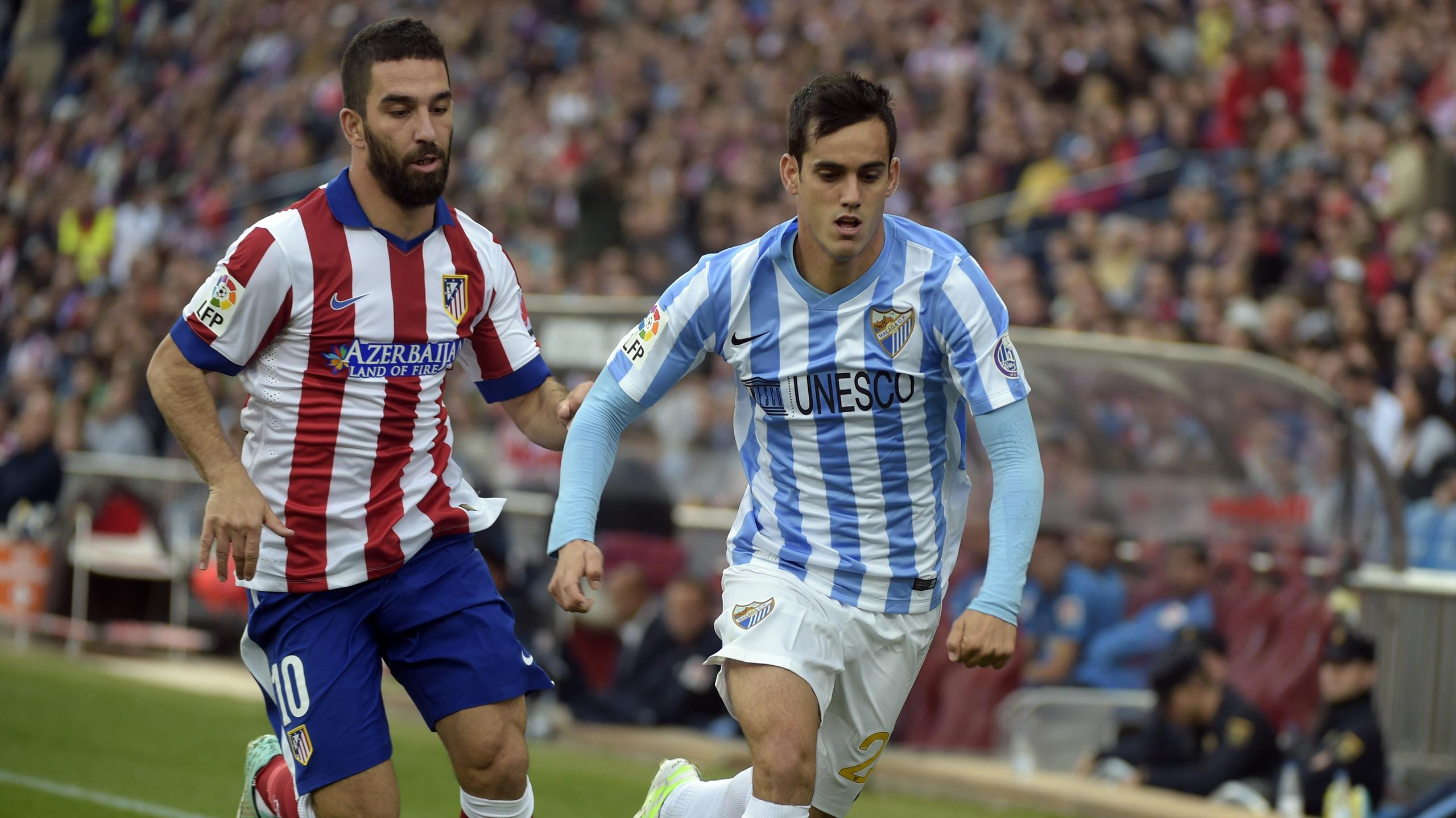 Malaga forward Juanmi is tracked by Atletico Madrid's Arda Turan