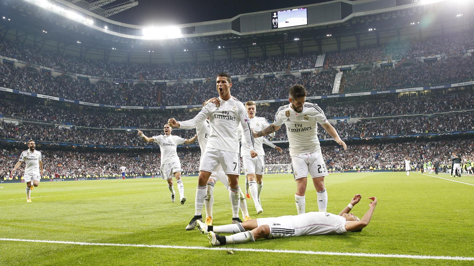 Cristiano Ronaldo celebrates Real Madrid's goal against Atletico while the scorer Javier Hernandez lies on the ground