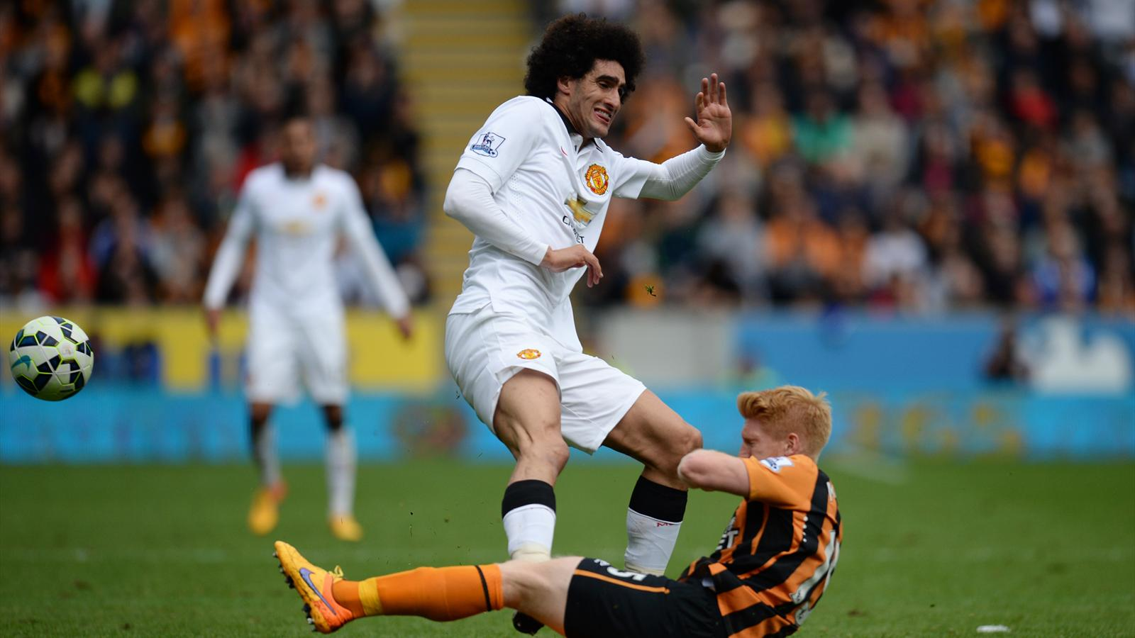 Manchester United's Belgian midfielder Marouane Fellaini (L) comes in late to foul Hull City's Irish defender Paul McShane