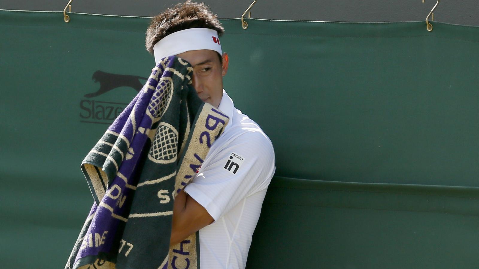 Kei Nishikori of Japan wipes his face during his men's singles tennis match against Milos Raonic
