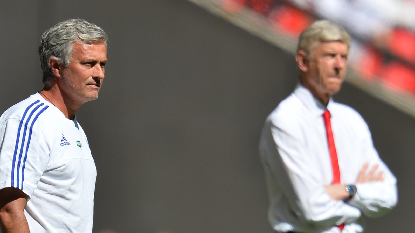 Chelsea's Portuguese manager Jose Mourinho (L) and Arsenal's French manager Arsene Wenger (R) watch from the side during the FA Community Shield football match between Arsenal and Chelsea at Wembley Stadium in north London on August 2, 2015