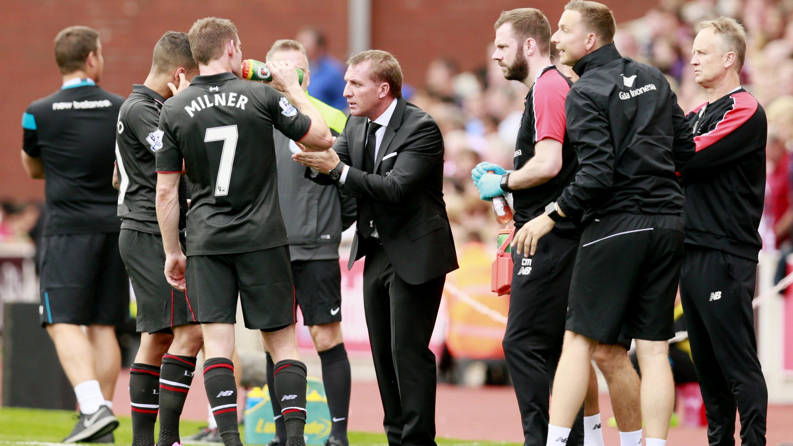 Liverpool manager Brendan Rodgers speaks with James Milner and Philippe Coutinho