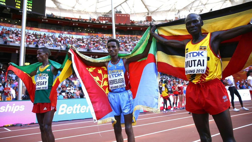 Winner Ghirmay Ghebreslassie of Eritrea (C), second placed Yemane Tsegay of Ethiopia (L) and third placed Munyo Solomon Mutai of Uganda celebrate with their national flags after crossing the finish line in the men's marathon.