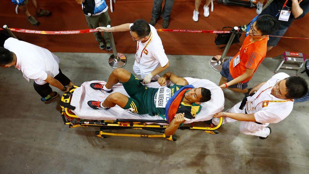 Wayde van Niekerk of South Africa is taken away by the medical team