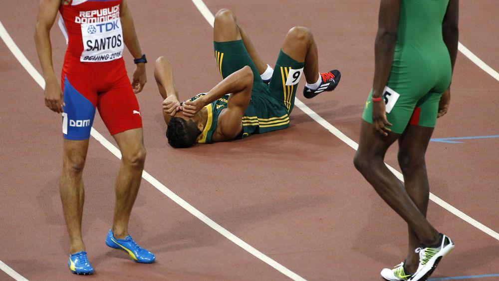 Wayde van Niekerk of South Africa falls to the ground after winning the men's 400 metres