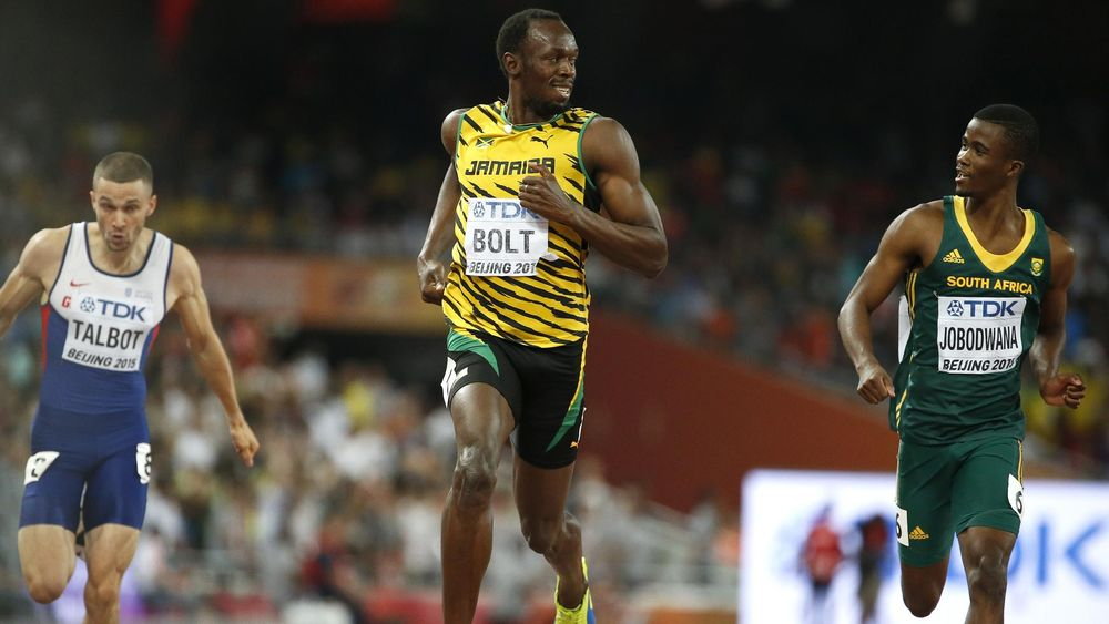 Usain Bolt of Jamaica (C) reacts after he wins the men's 200 metres semi-finals ahead of Anaso Jobodwana of South Africa (R) during the 15th IAAF World Championships at the National Stadium in Beijing, China August 26, 2015