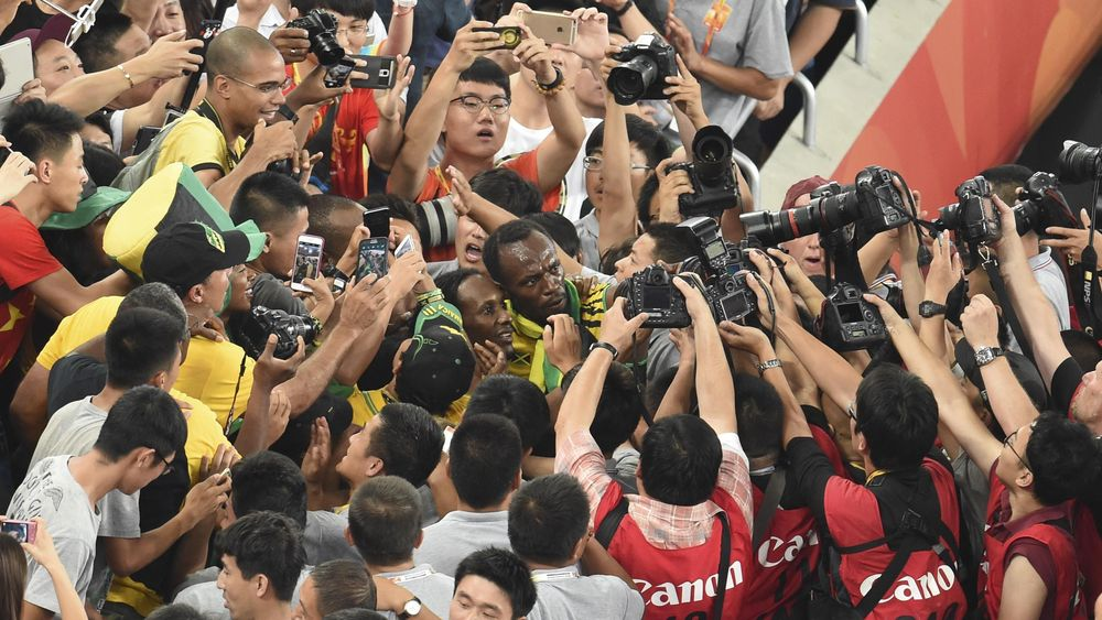 """Jamaica's Usain Bolt (C) celebrates with fans after winning the final of the men's 200 metres athletics event at the 2015 IAAF World Championships at the """"Bird's Nest"""" National Stadium in Beijing on August 27, 2015"""