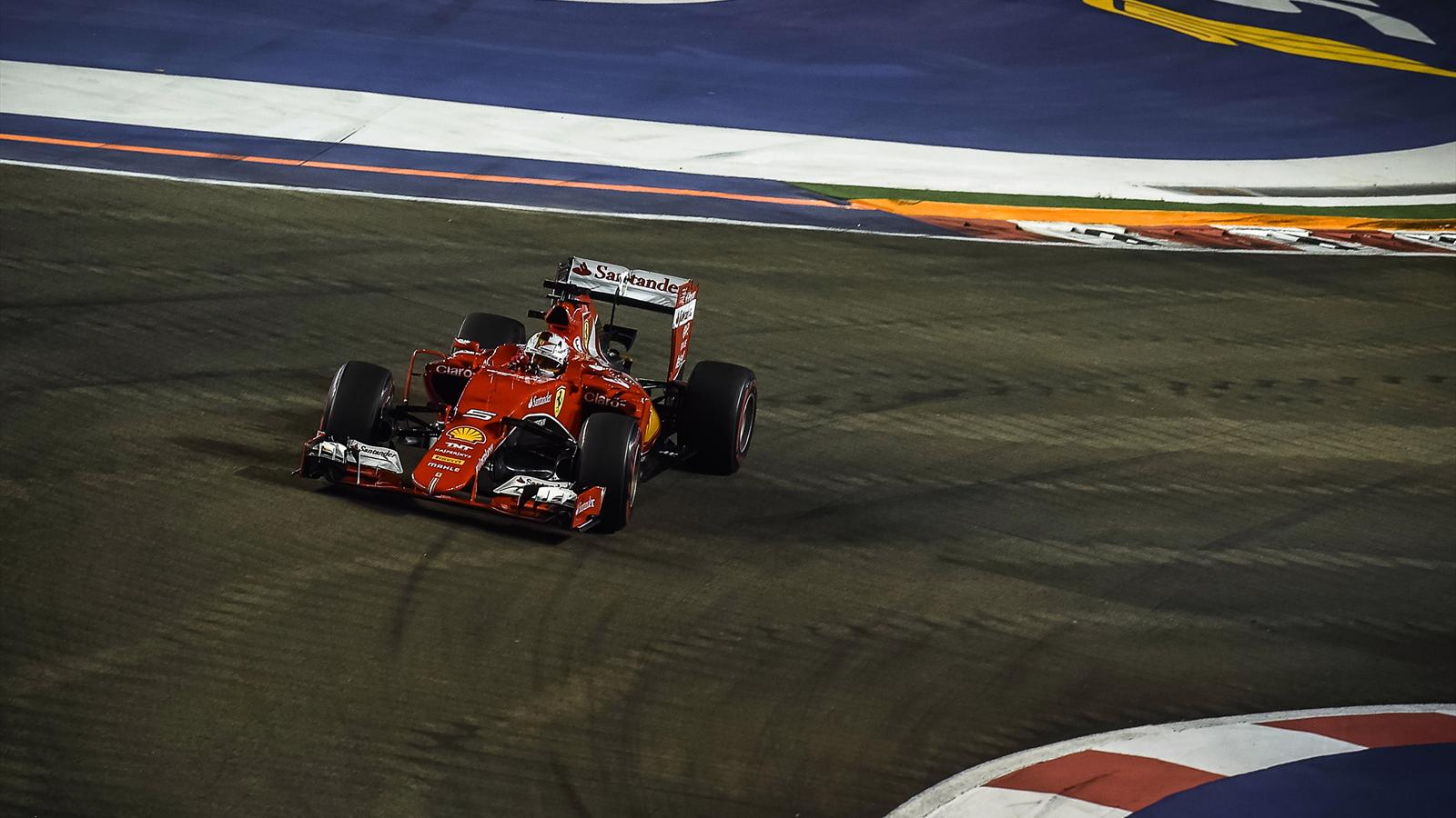 Ferrari's German driver Sebastian Vettel powers his car during the Formula One Singapore Grand Prix in Singapore on September 20, 2015