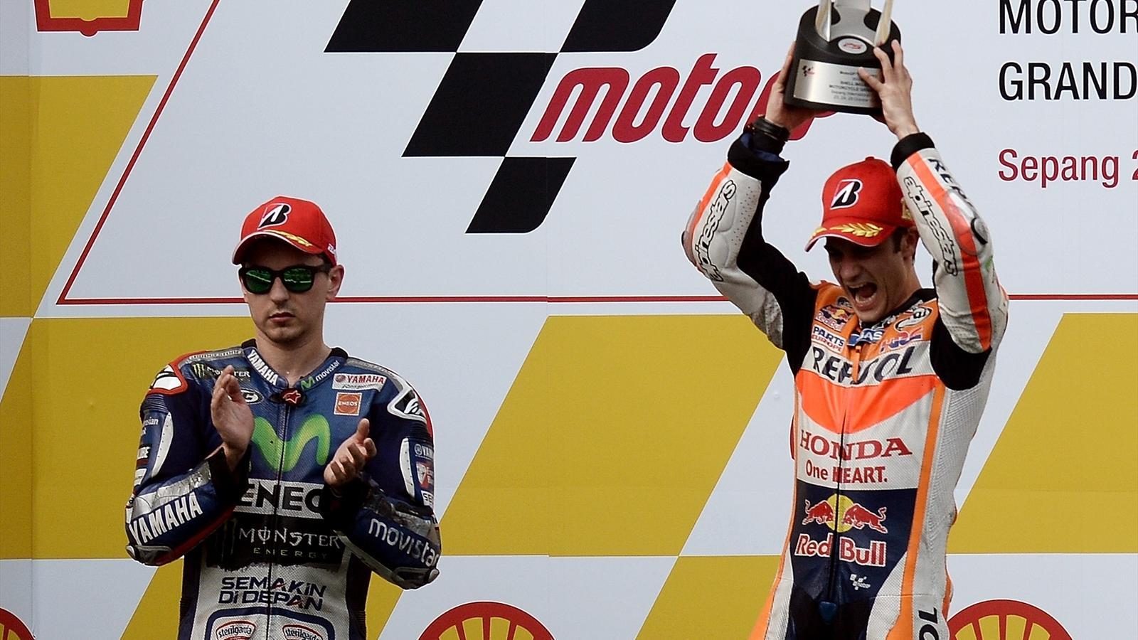 Jorge Lorenzo claps as Dani Pedrosa celebrates on the podium in Malaysia