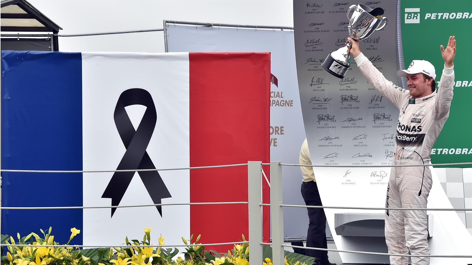 Mercedes' Formula One German driver Nico Rosberg celebrates after winning the Brazilian Grand Prix, beside a French flag with a black ribbon to remember those people killed during the Paris November 13 attacks, at the Interlagos racetrack in Sao Paulo, on