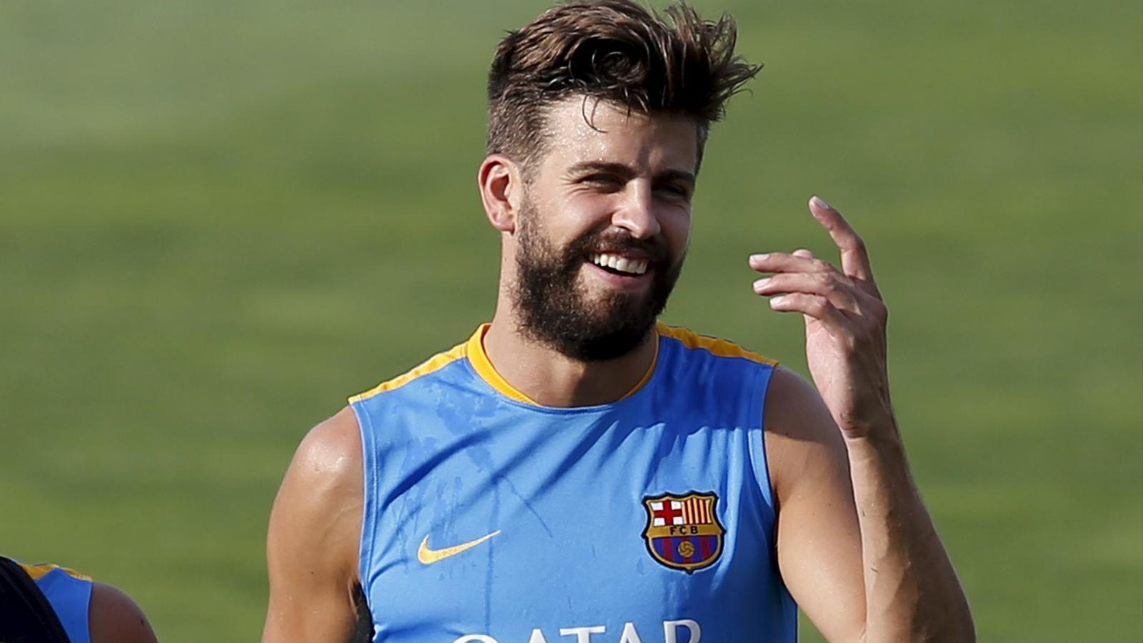 Barcelona defender Gerard Pique laughs during training