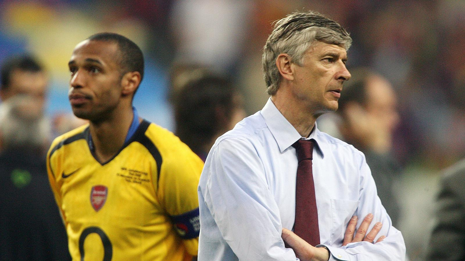 Arsenal's Thierry Henry of France (L) and manager Arsene Wenger, also of France, stand on the pitch after losing the Champions League final