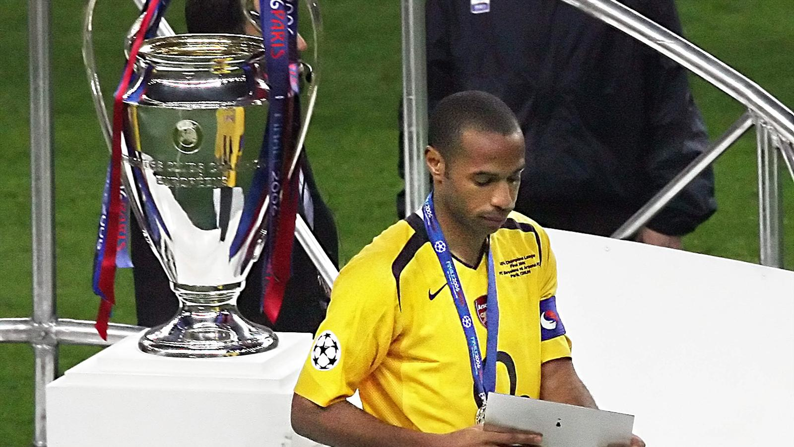 Arsenal's French forward and team captain Thierry Henry passes next to the UEFA Champion's League trophy