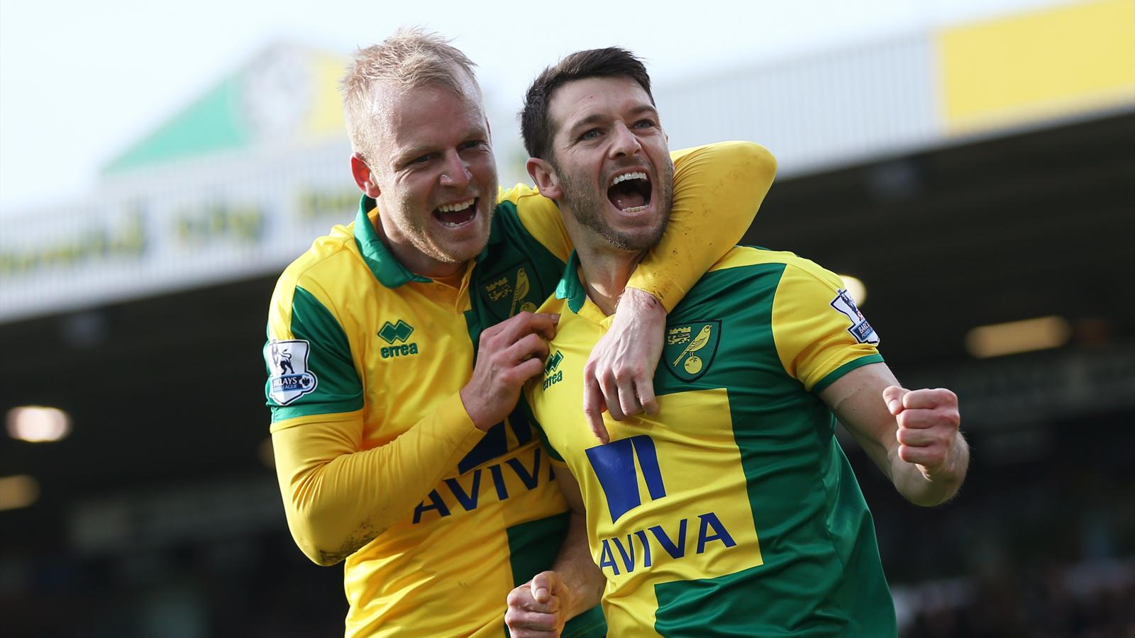 Wes Hoolahan celebrates with Steven Naismith after scoring the third goal for Norwich from the penalty spot