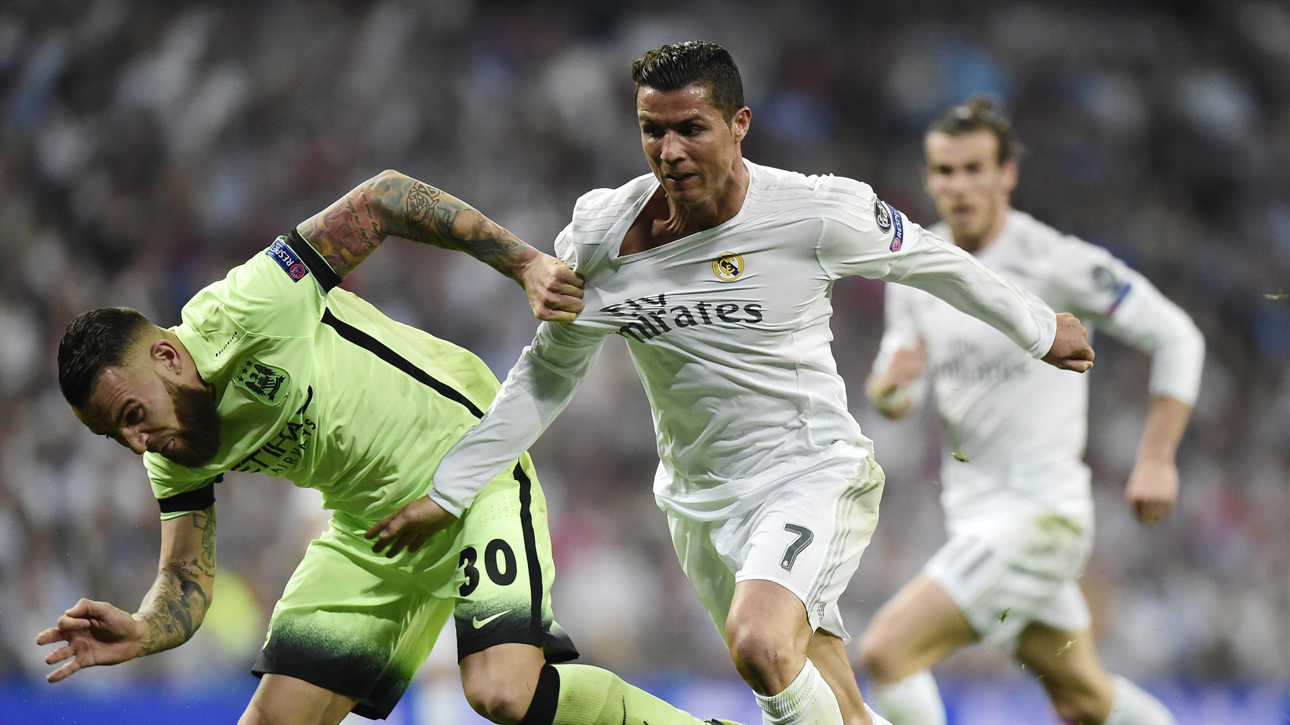 Real Madrid's Portuguese forward Cristiano Ronaldo (C) vies with Manchester City's Argentinian defender Nicolas Otamendi (L)