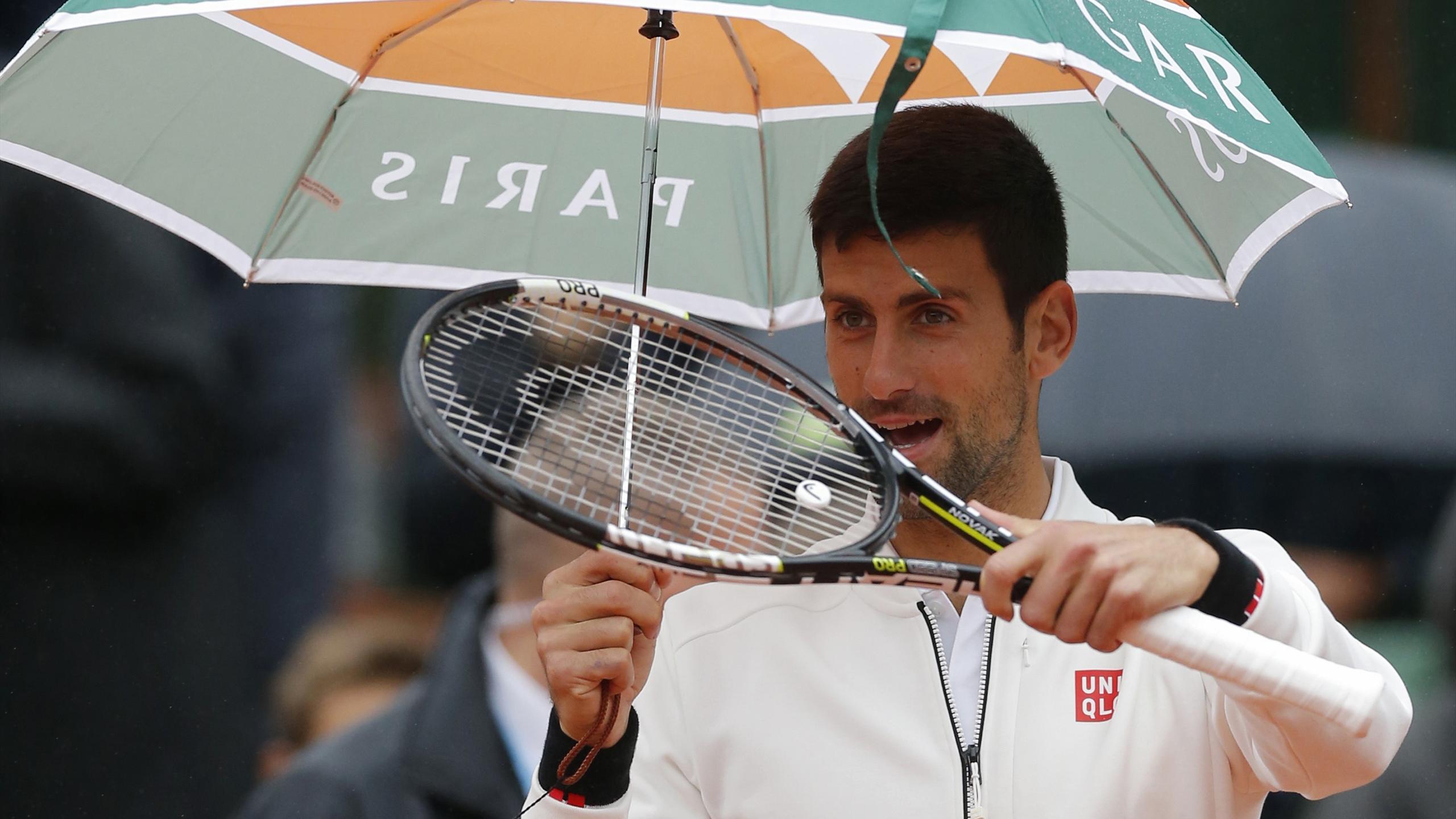 Novak Djokovic holds an umbrella as he arrives on the court.