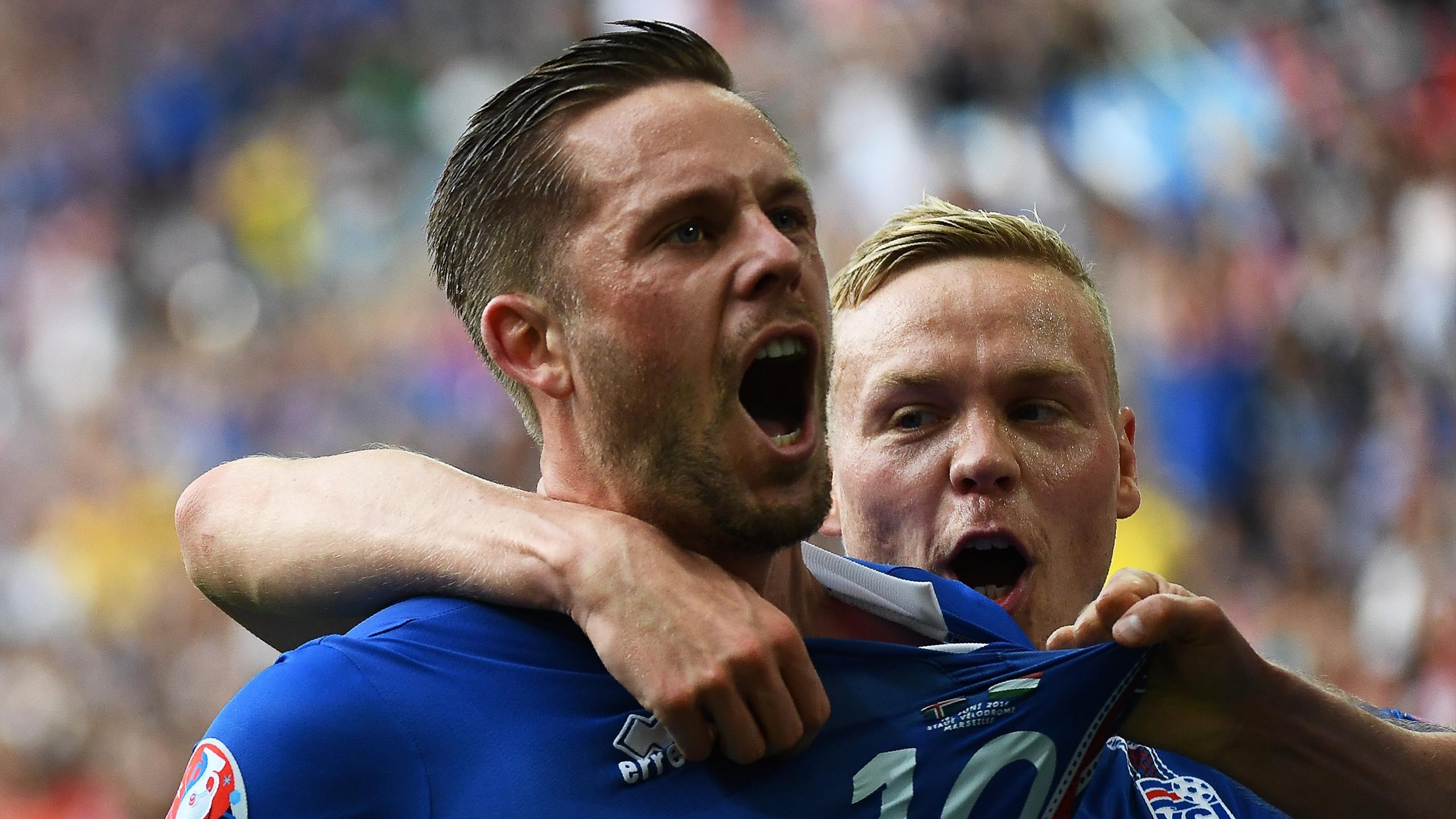 Iceland's midfielder Gylfi Sigurdsson (L) celebrates after scoring his team's first goal