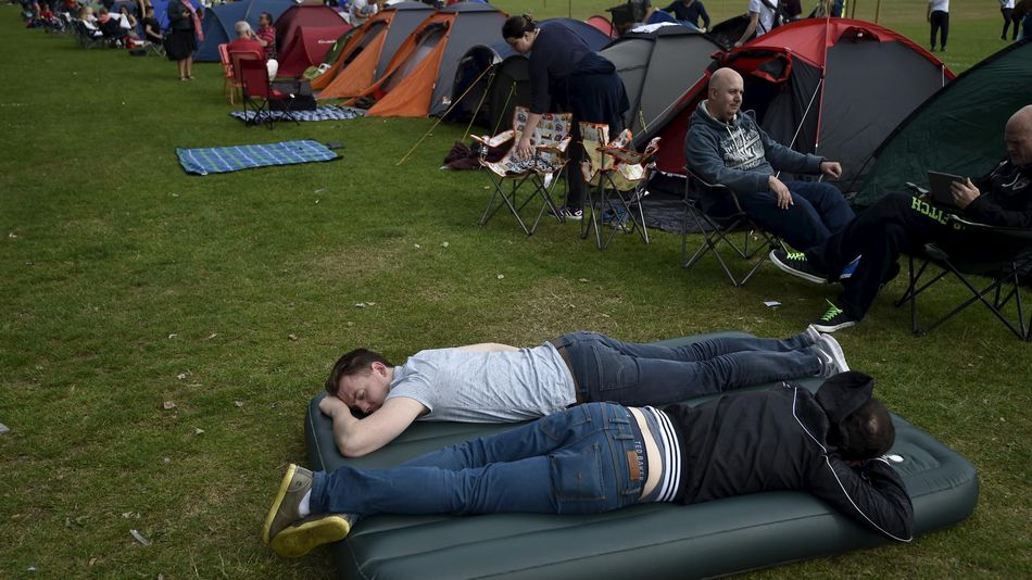 Tennis fans relax after setting up their tents in the ticket queue at Wimbledon