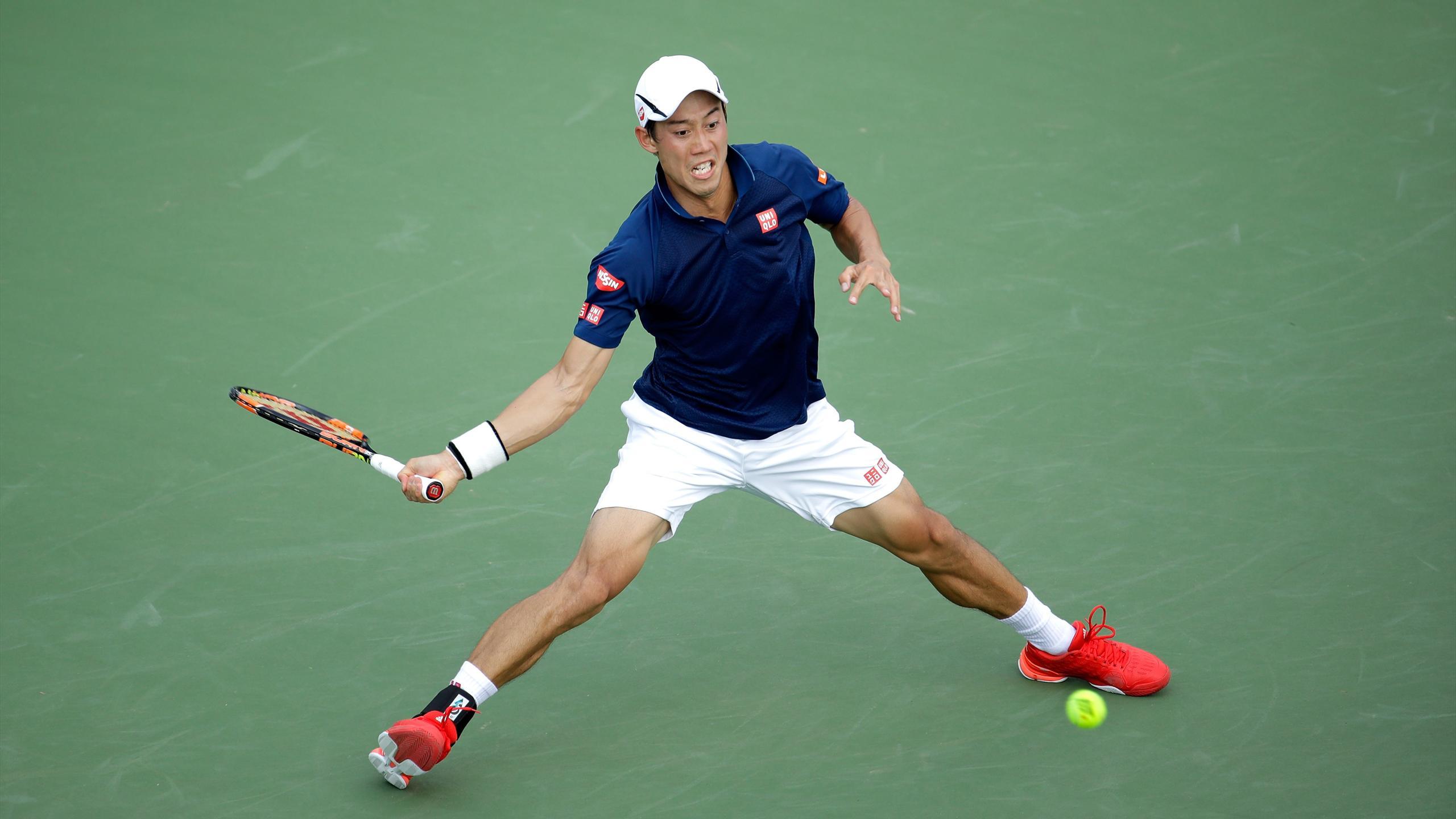 Kei Nishikori hits a return during his third round match against Bernard Tomic