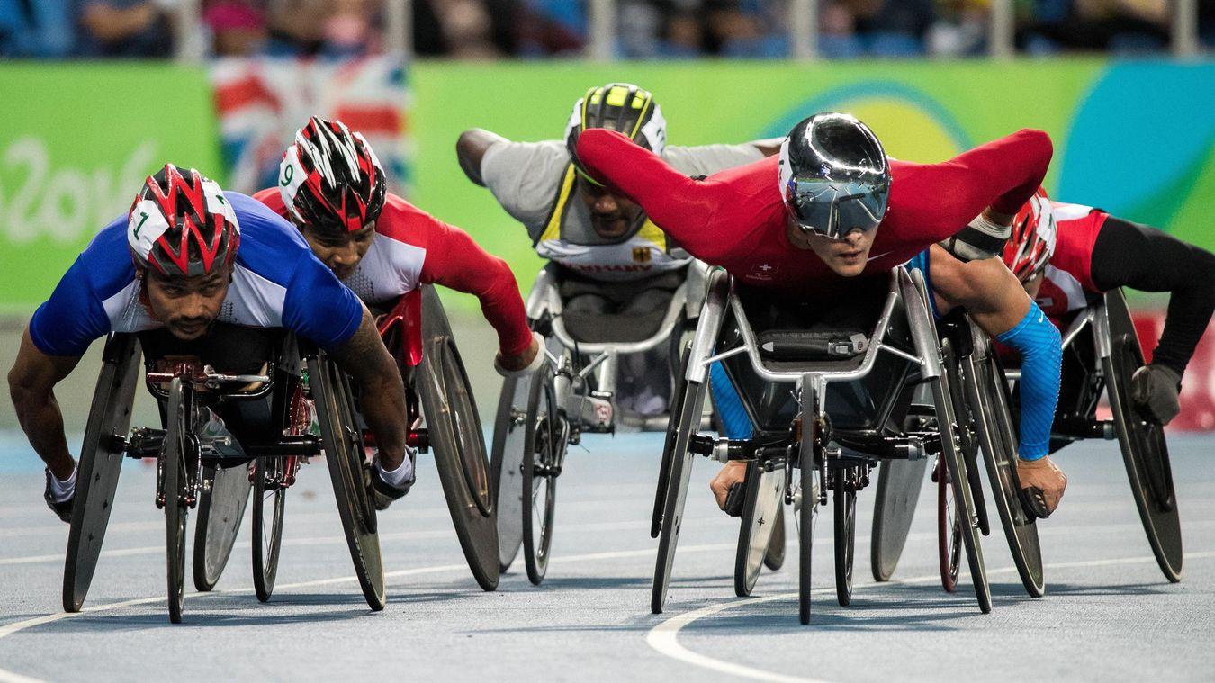 Seis atletas usando óculos escuros e capacete, movimenta uma cadeira de rodas numa pista