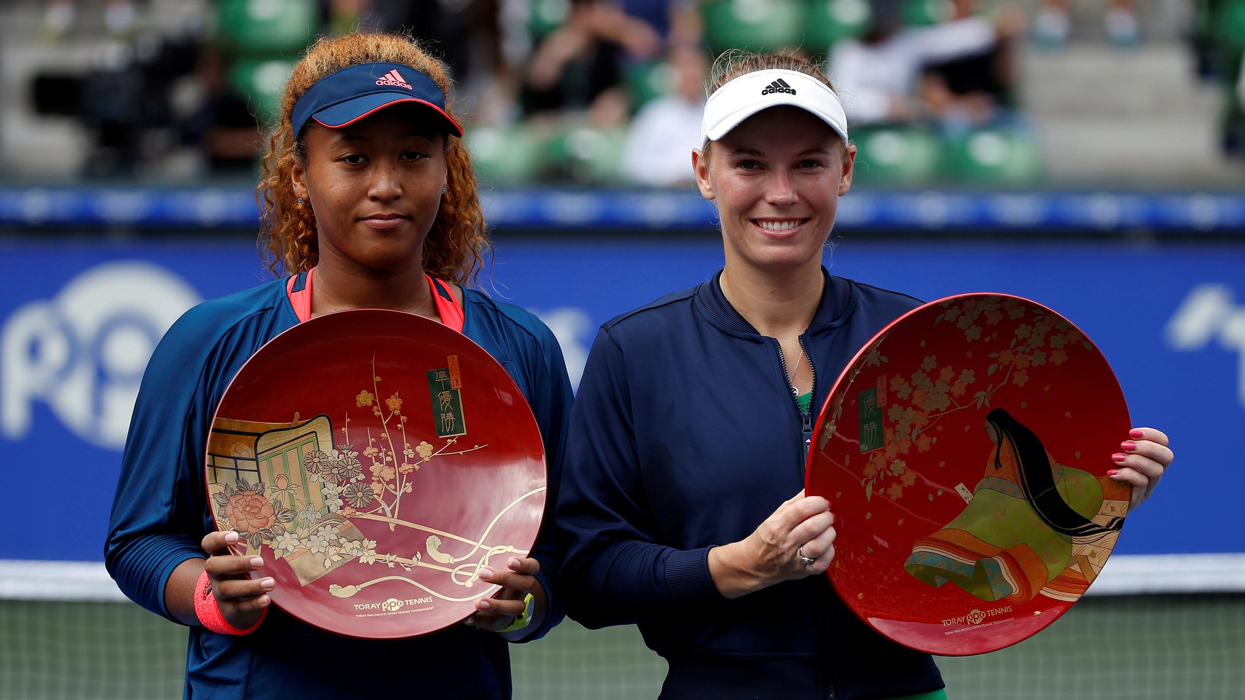 Caroline Wozniacki of Denmark, flanked by second-placed Naomi Osaka of Japan, holds a winning plate during an awarding ceremony after winning the final match