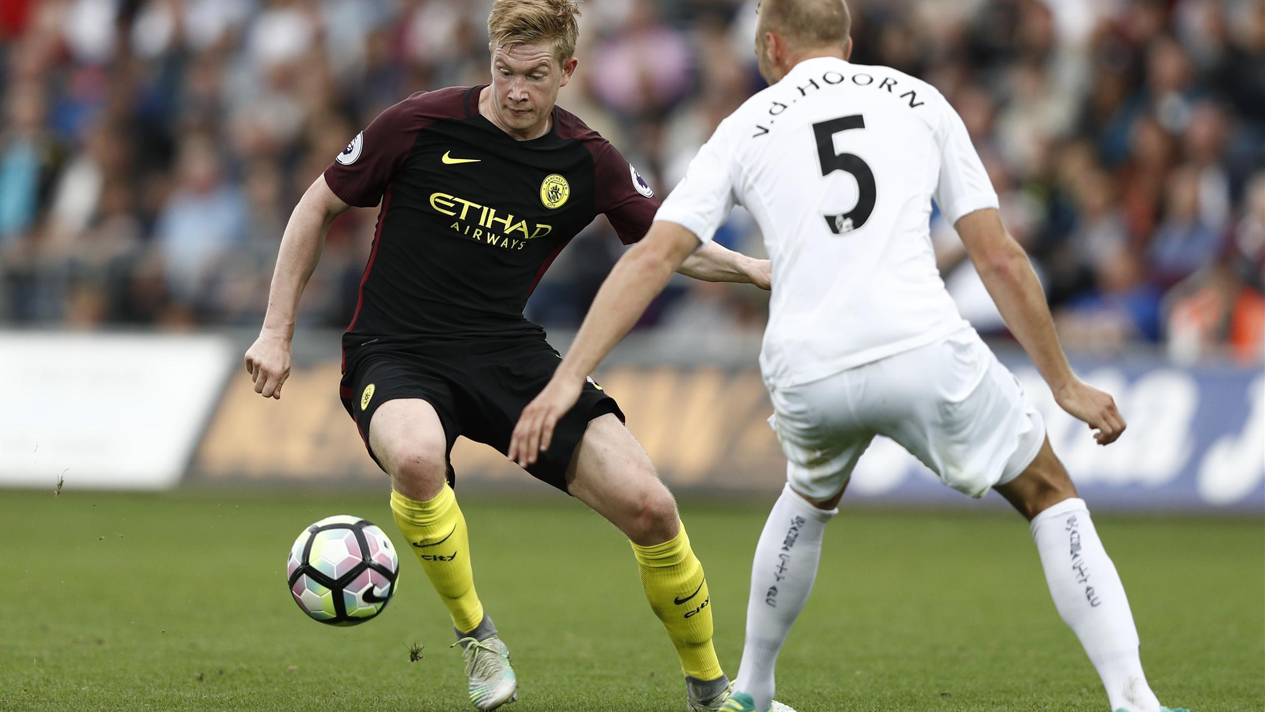 Manchester City's Belgian midfielder Kevin De Bruyne (L) takes on Swansea City's Dutch defender Mike van der Hoorn