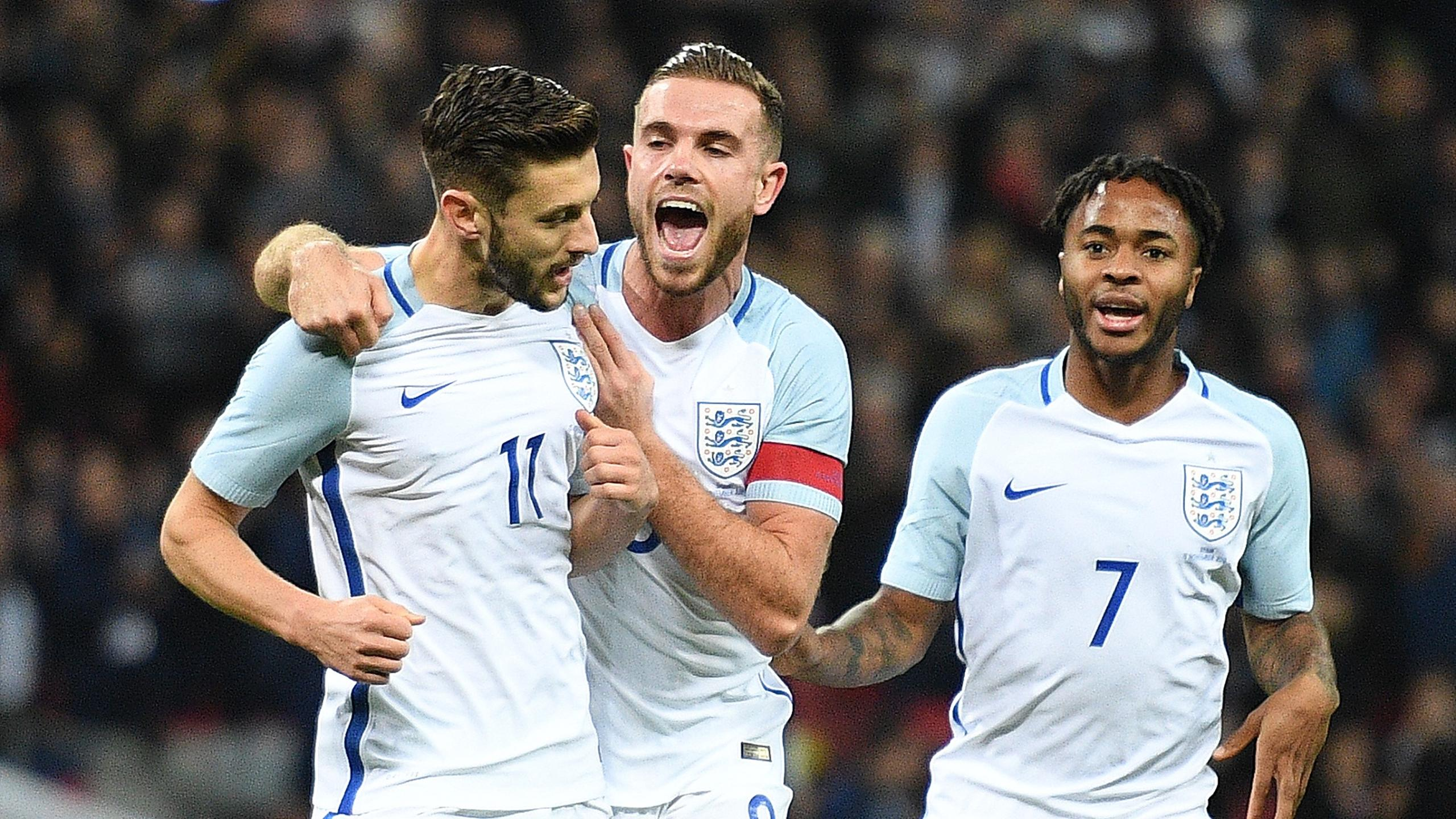 England's midfielder Adam Lallana (L) celebrates scoring his team's first goal from the penalty spot with England's midfielder Jordan Henderson (C) and England's midfielder Raheem Sterling