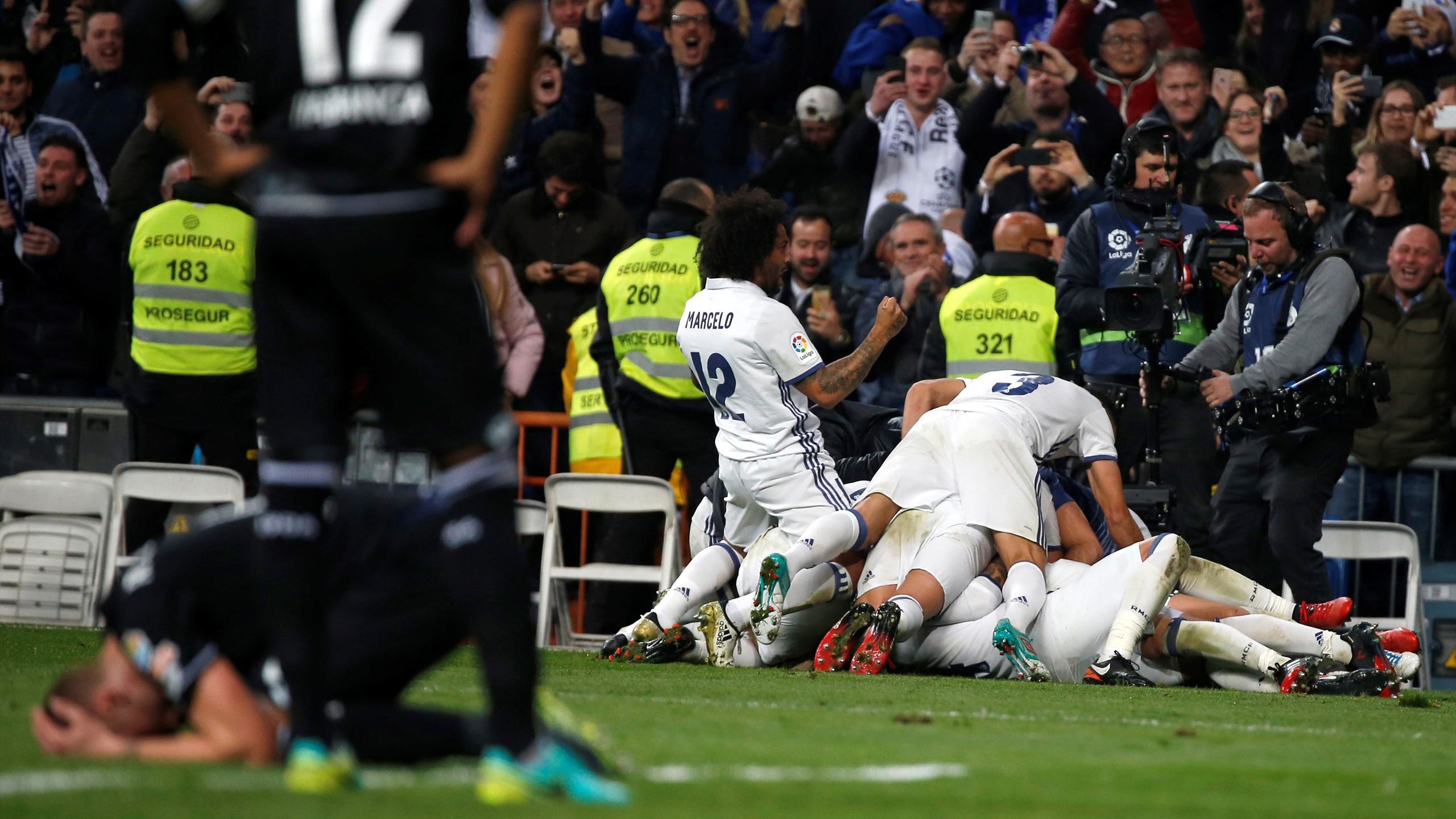 Real Madrid players celebrate Sergio Ramos' winning goal against Deportivo