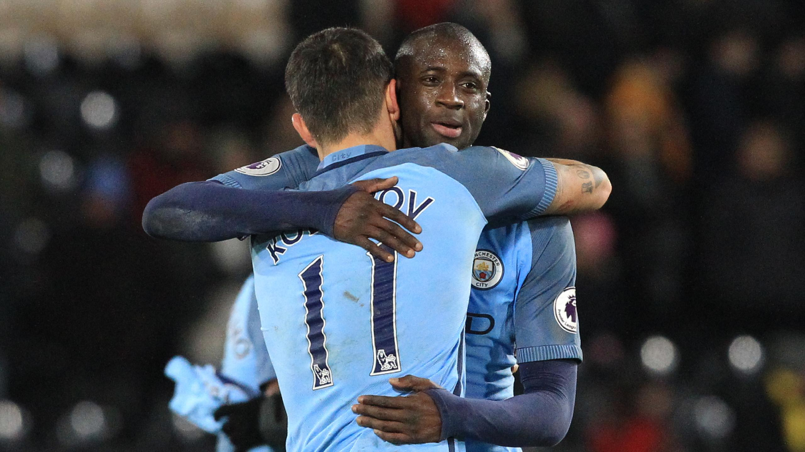 Manchester City's Ivorian midfielder Yaya Toure (R) embraces Manchester City's Serbian defender Aleksandar Kolarov (L)