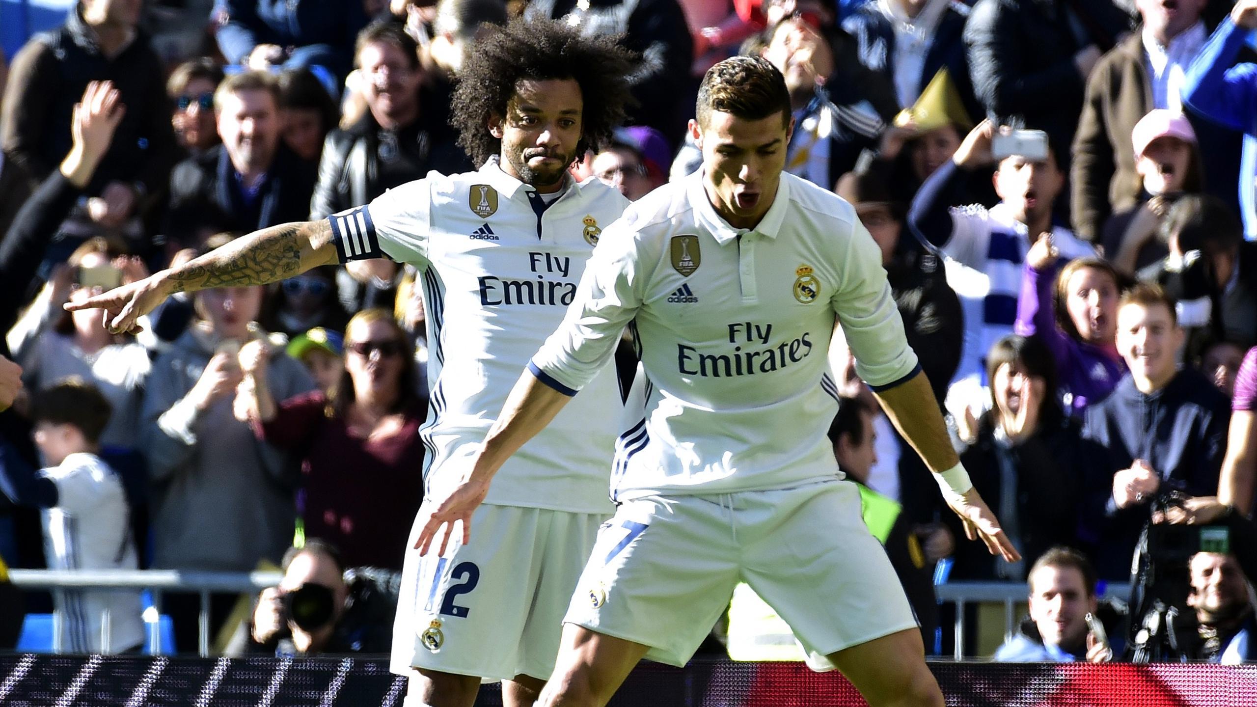 Real Madrid's Portuguese forward Cristiano Ronaldo (front) celebrates past Real Madrid's Brazilian defender Marcelo
