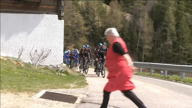 Una vecchietta attraversa la strada davanti al gruppo al Tour of the Alps