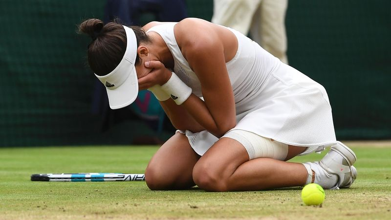 Garbiñe Muguruza sinks to her knees after winning Wimbledon.