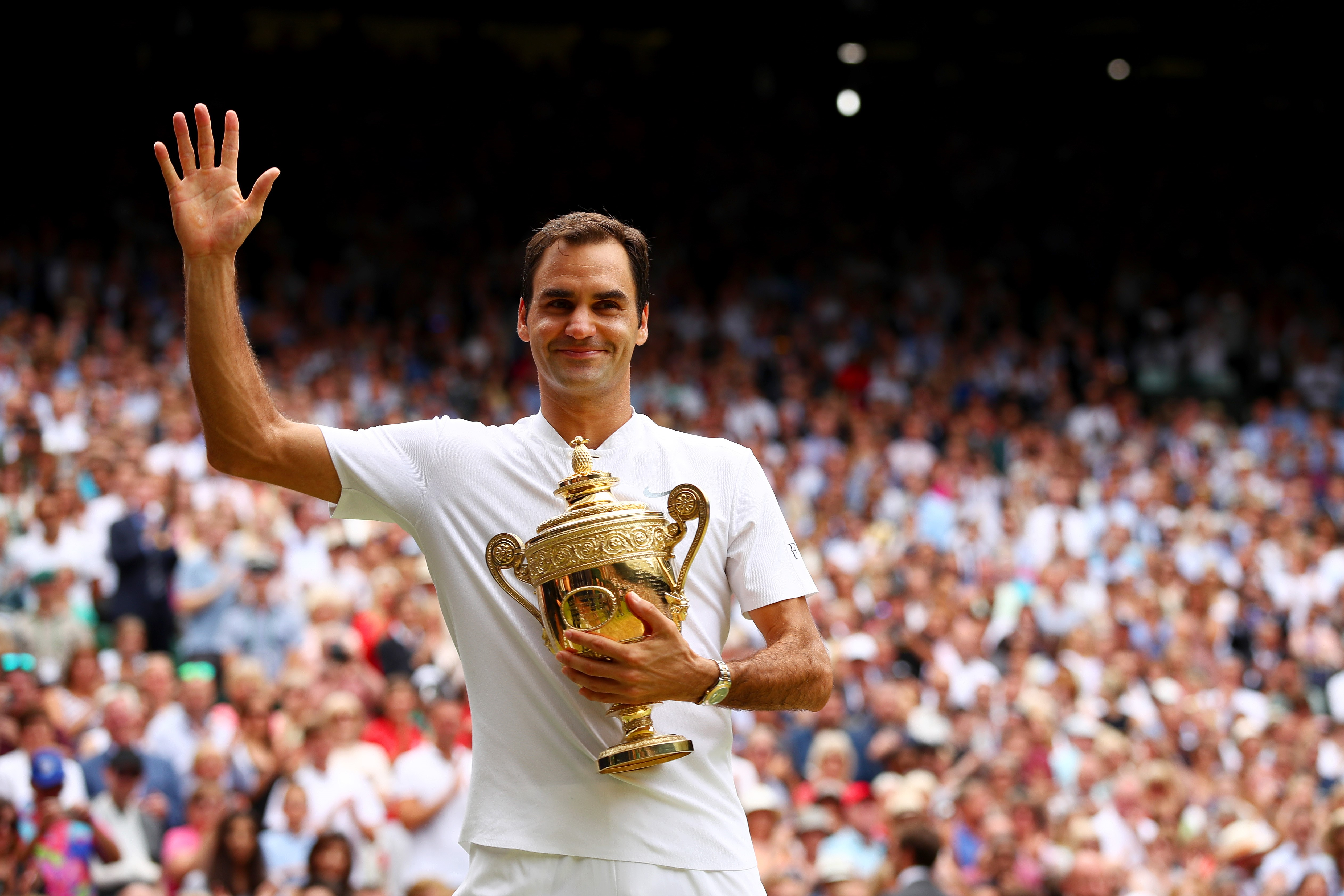 Roger Federer celebrates with the Wimbledon trophy