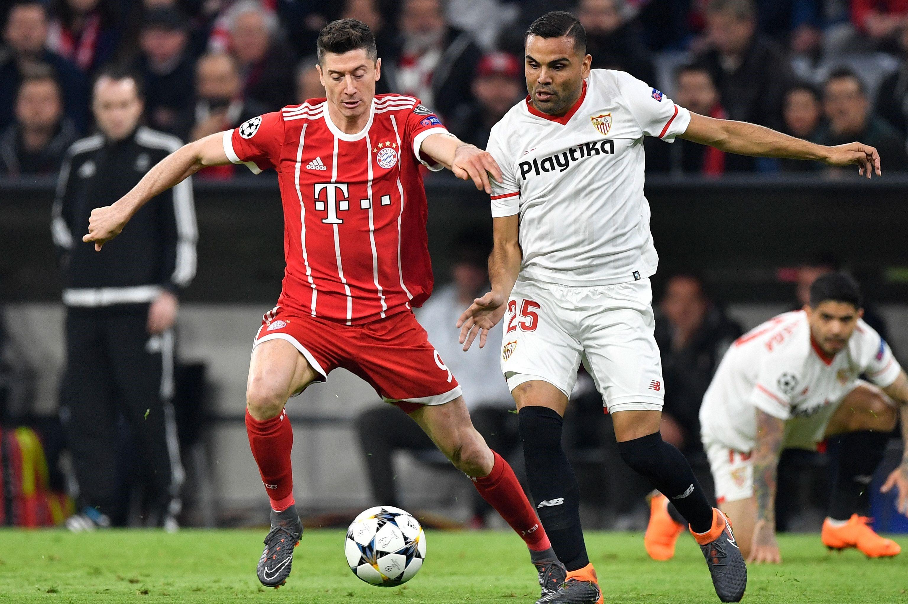 Lewandowski, del Bayern, y Mercado, del Sevilla, pugnan por un balón