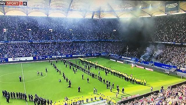 Los aficionados del Hamburgo arrojan bengalas de humo negro en protesta por el descenso