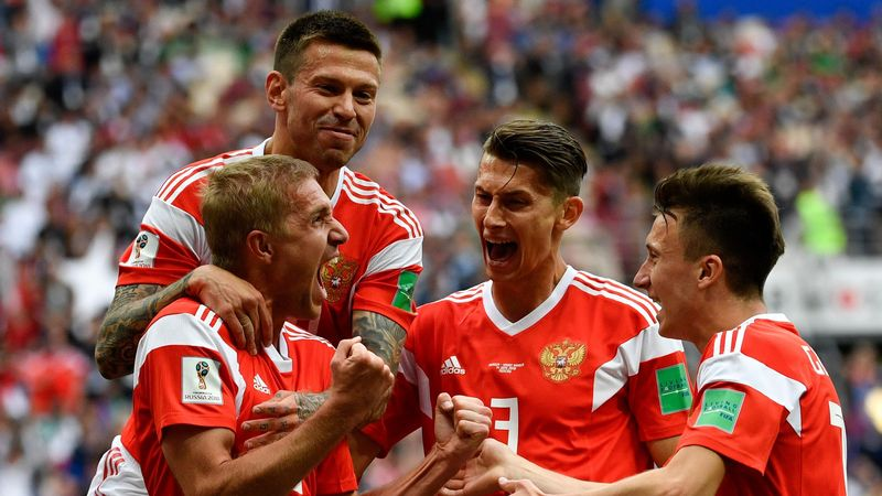 Russia's midfielder Yuri Gazinskiy (L) celebrates scoring the opening goal with his teammates during the Russia 2018 World Cup Group A football match between Russia and Saudi Arabia at the Luzhniki Stadium in Moscow on June 14, 2018