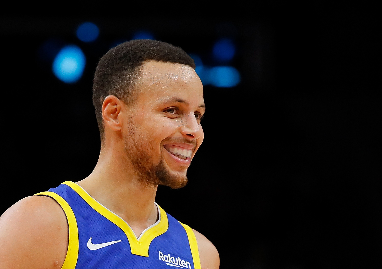 Stephen Curry, tout sourire sous le maillot de Golden State lors de la saison 2018-2019 de NBA.