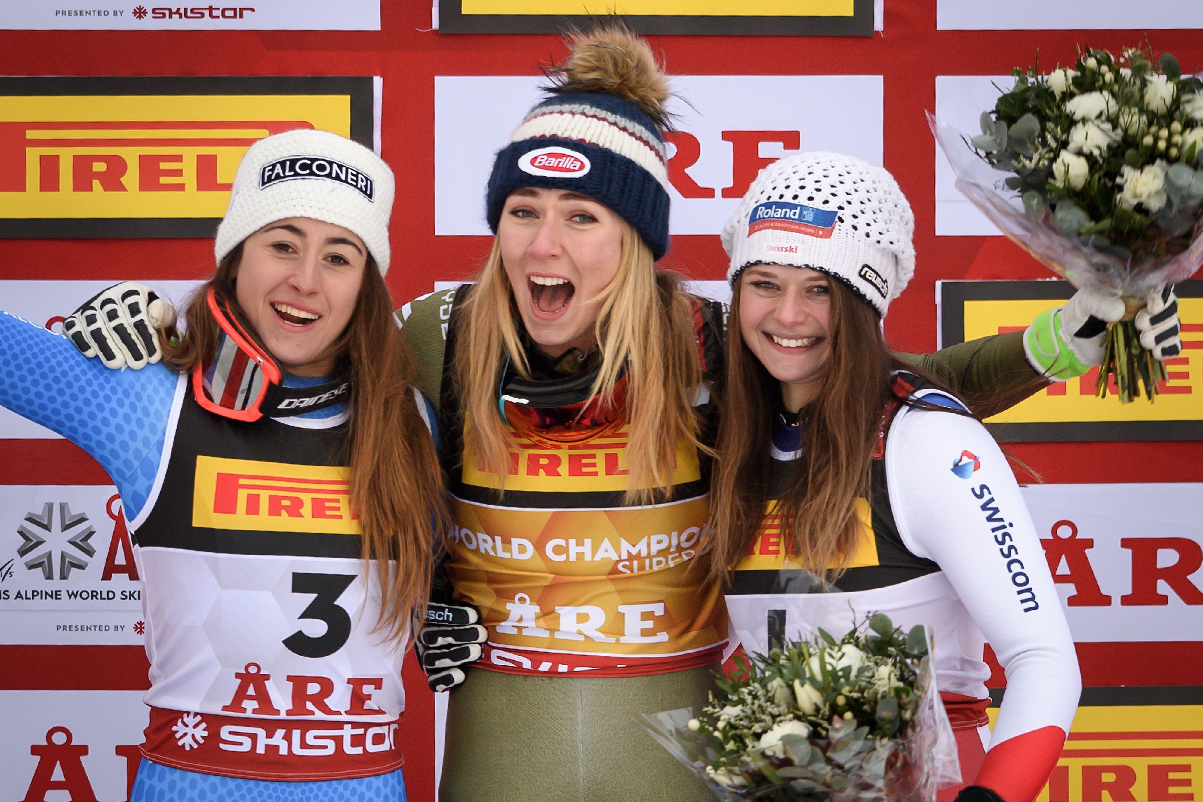 Silver medallist Italys Sofia Goggia, gold medallist US Mikaela Shiffrin and bronze medallist Switzerland's Corinne Suter celebrate during the flower ceremony of the women's Super G event of the 2019 FIS Alpine Ski World Championships at the National Aren