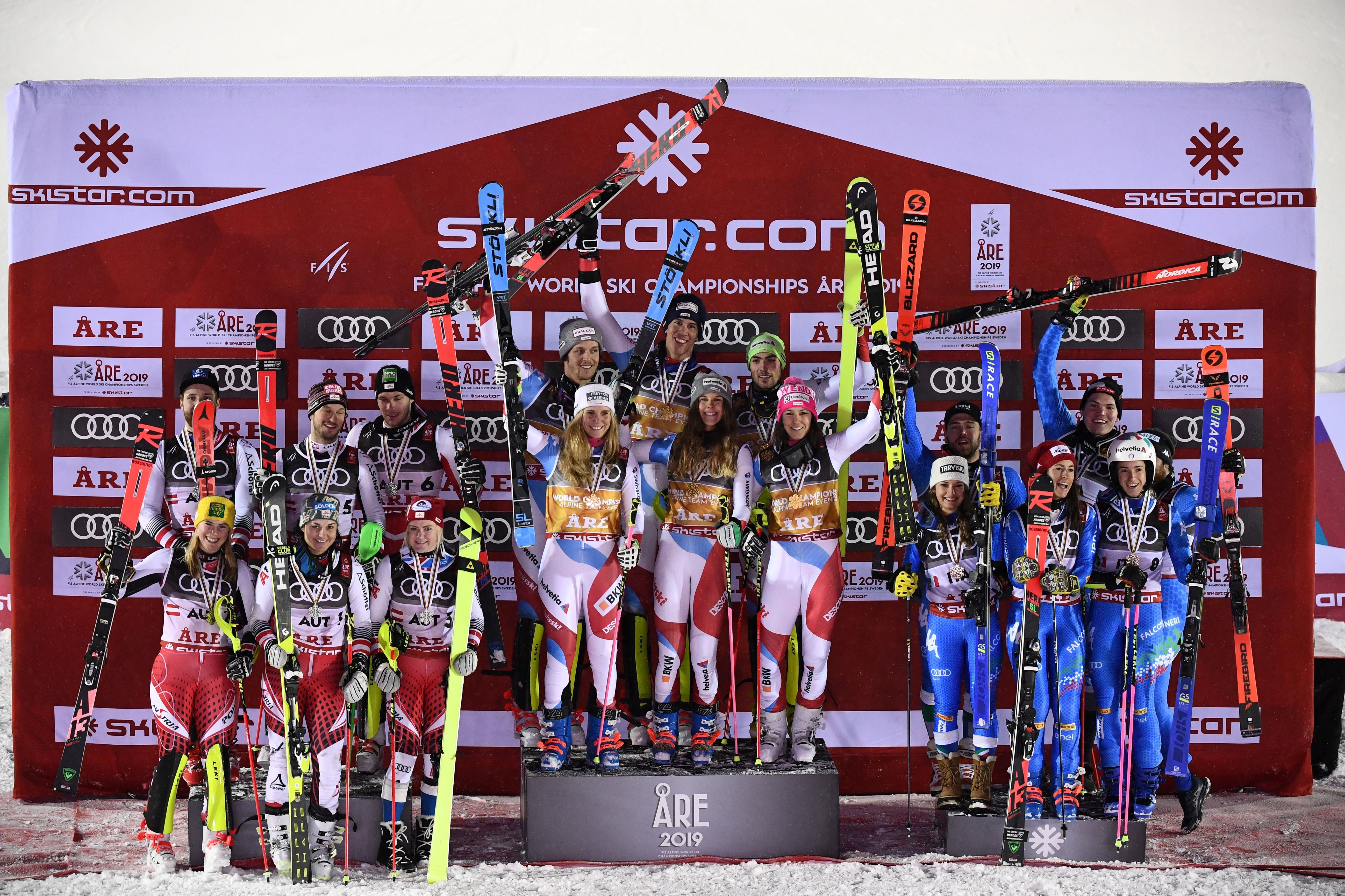 Winner Swiss team (C), second-placed Autrian team and third-placed Italian team celebrate after the Alpine team event at the 2019 FIS Alpine Ski World Championships at the National Arena in Are, Sweden, on February 12, 2019.