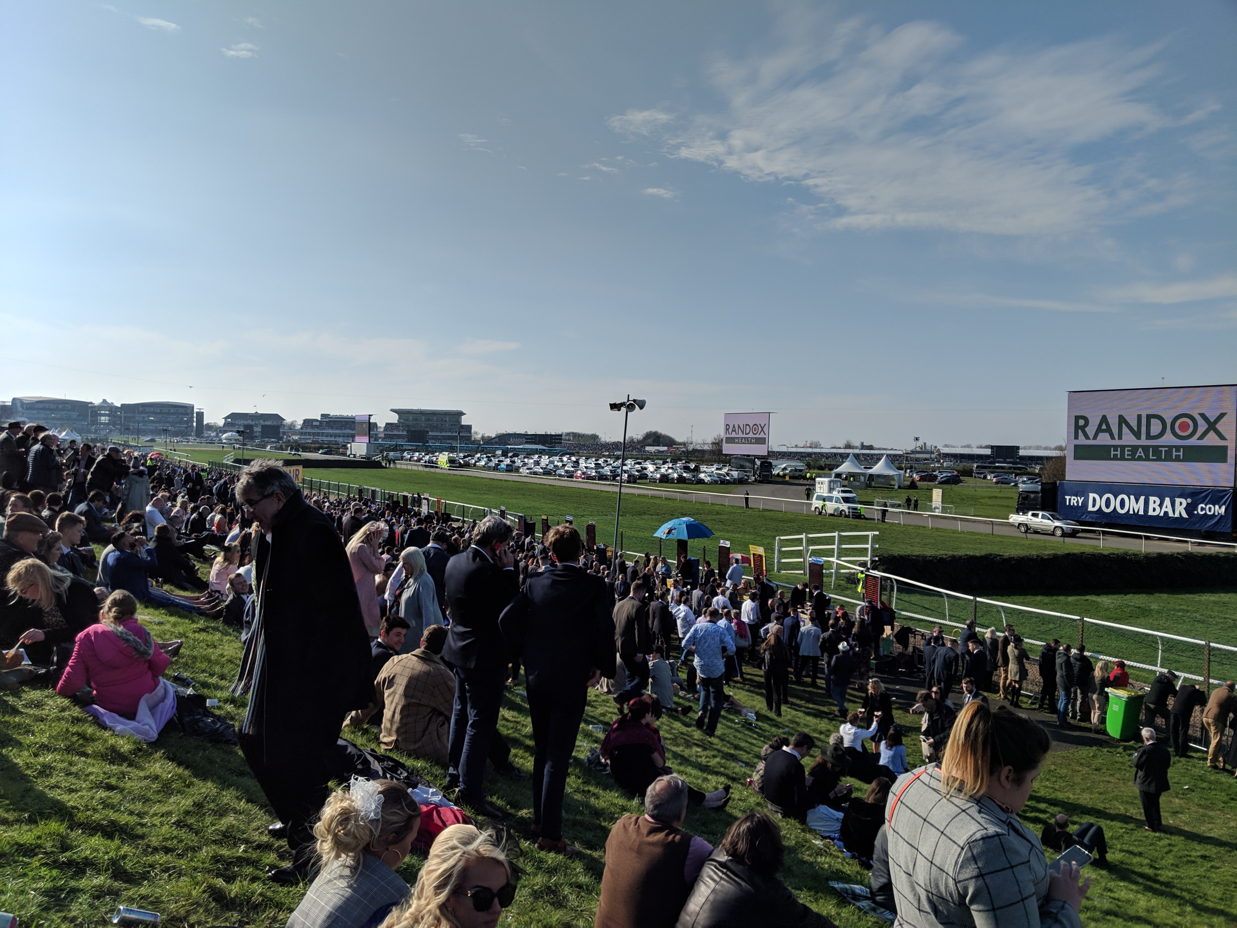 Steeple Enclosure'de çimlere serilmiş seyirciler Grand National yarışının startını bekliyor. (Bu görsel The Jockey Club'ın izniyle kullanılmıştır)