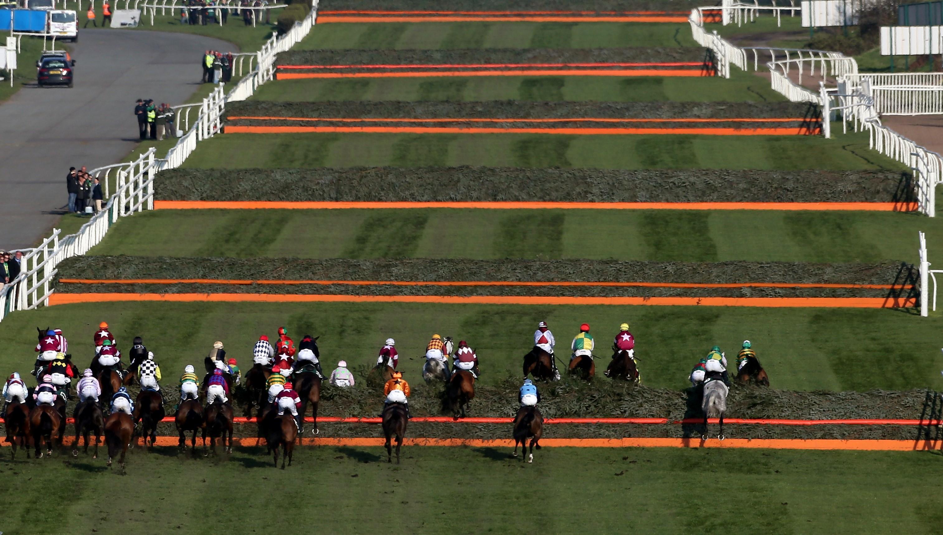 Grand National'ın start düzlüğünde atlar peş peşe altı engel geçiyor. (Bu görsel The Jockey Club'ın izniyle kullanılmıştır)