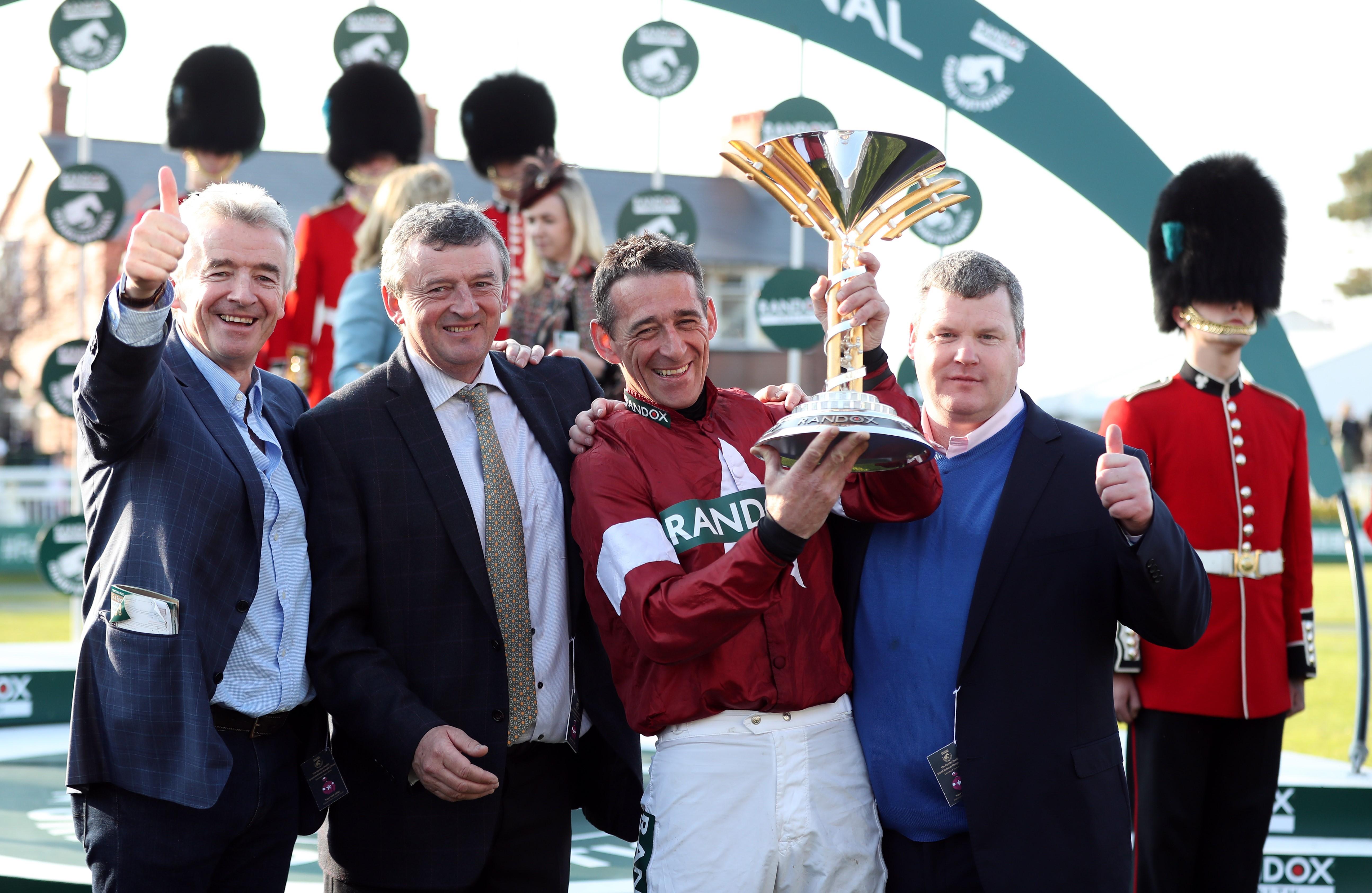 Şampiyonlar kupalarıyla: At sahibi Michael O'Leary, jokey Davy Russell ve antrenör George Elliott. (Bu görsel The Jockey Club'ın izniyle kullanılmıştır)