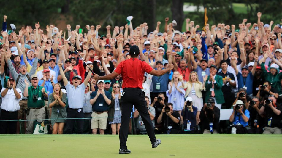 Tiger Woods of the United States celebrates after sinking his putt on the 18th green to win during the final round of the Masters at Augusta National Golf Club on April 14, 2019 in Augusta, Georgia