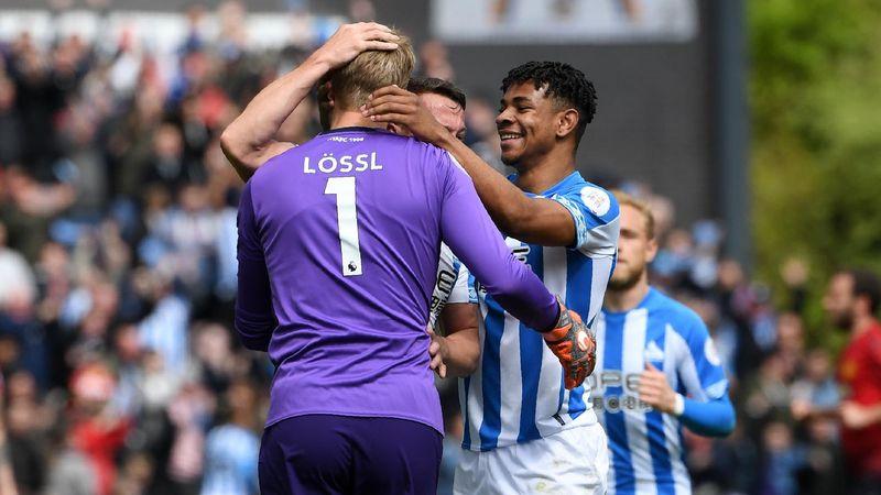 Huddersfield Town's Danish goalkeeper Jonas Lossl (L) is congratulated by teammates