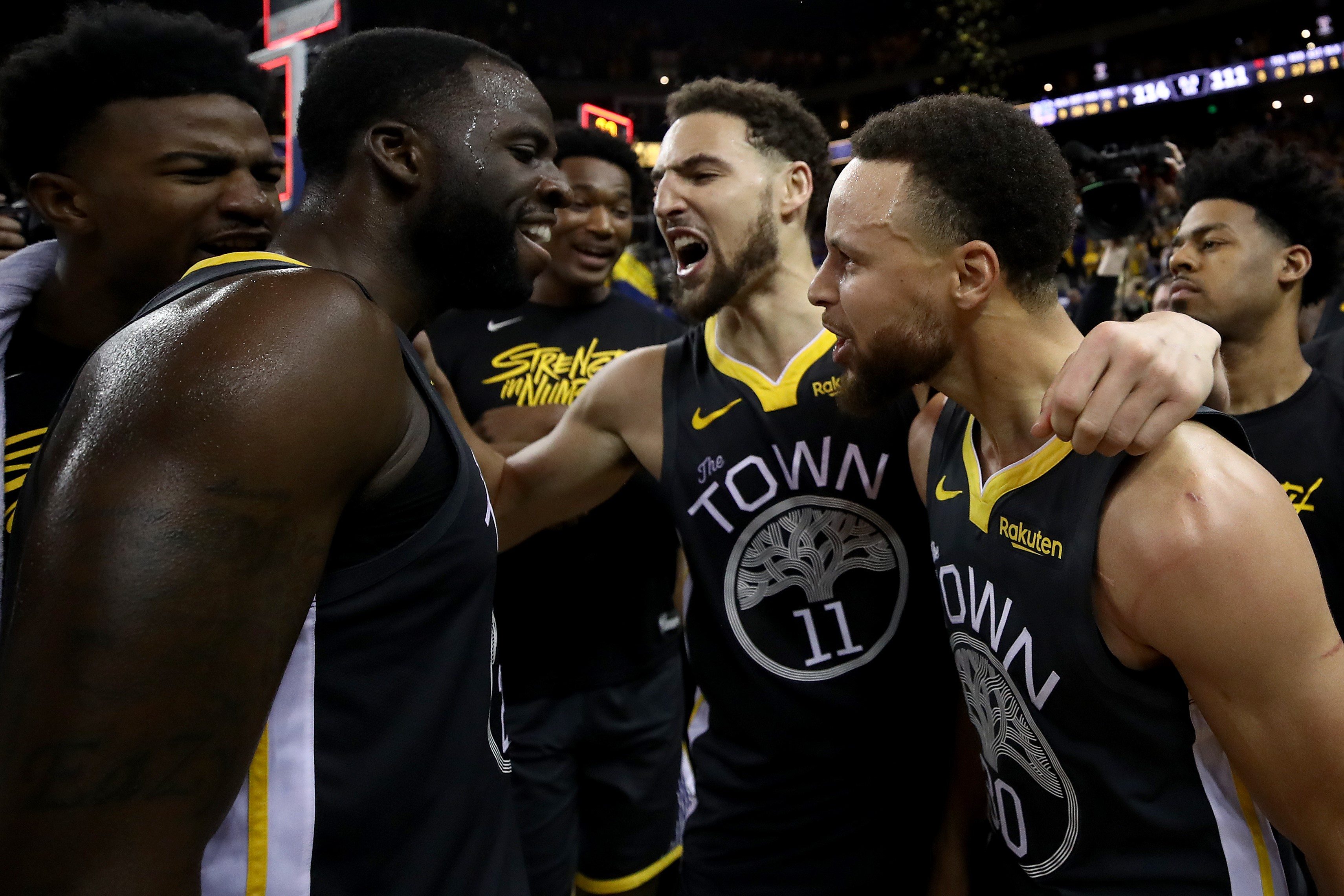 Stephen Curry #30, Klay Thompson #11 and Draymond Green #23 of the Golden State Warriors celebrate after defeating the Portland Trail Blazers 114-111 in game two of the NBA Western Conference Finals at ORACLE Arena on May 16, 2019 in Oakland