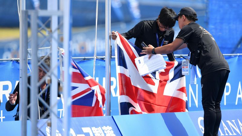 British national flags are removed as the medal ceremony is postponed after Jessica Learmonth and Georgia Taylor Brown of Great Britain were disqualified in the Women's Olympic Qualification event during the ITU Olympic Qualification at Odaiba Marine Park