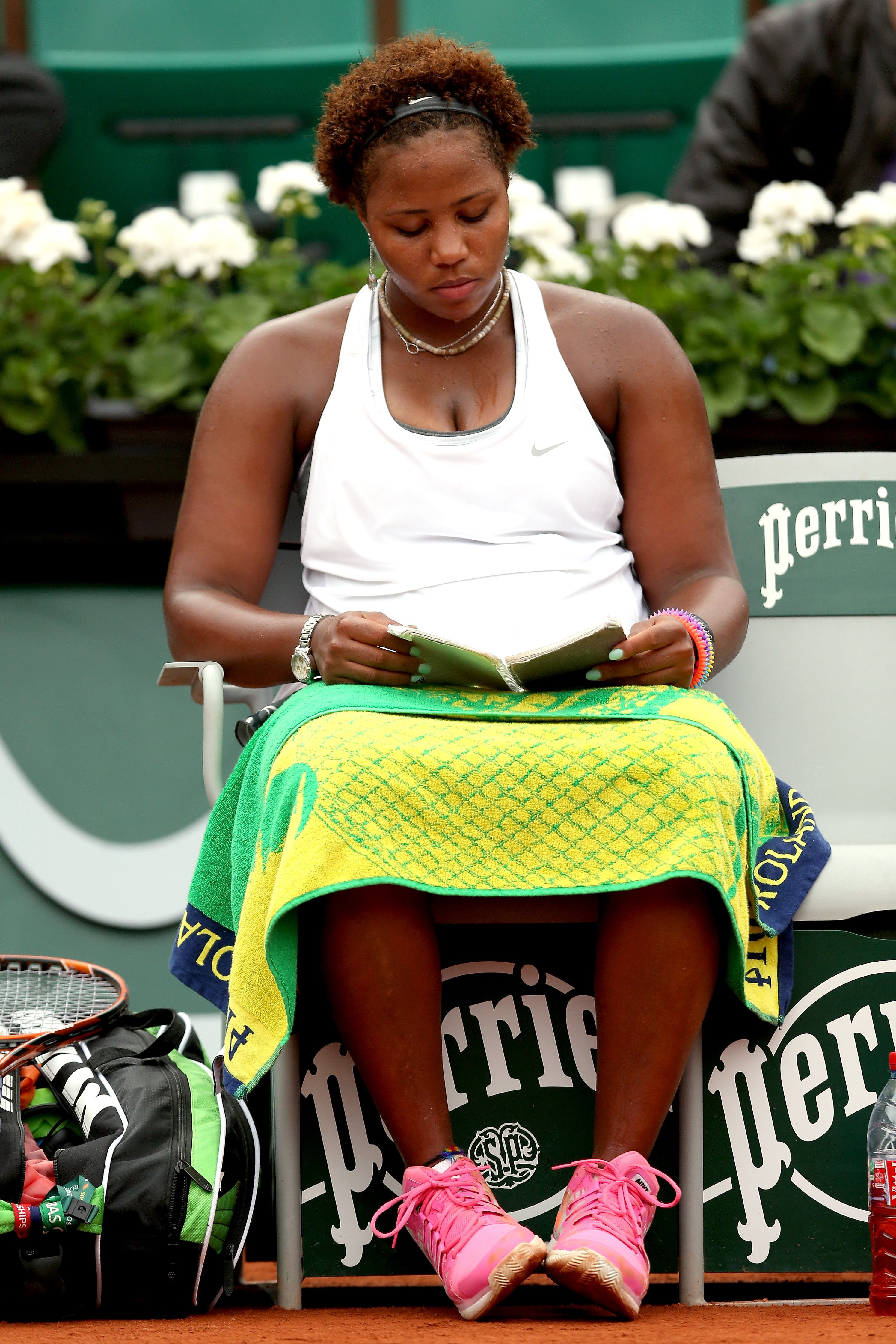 Taylor Townsend of the United States reads a book during a break in her women's singles match against Alize Cornet of France on day four of the French Open at Roland Garros on May 28, 2014 in Paris, France.