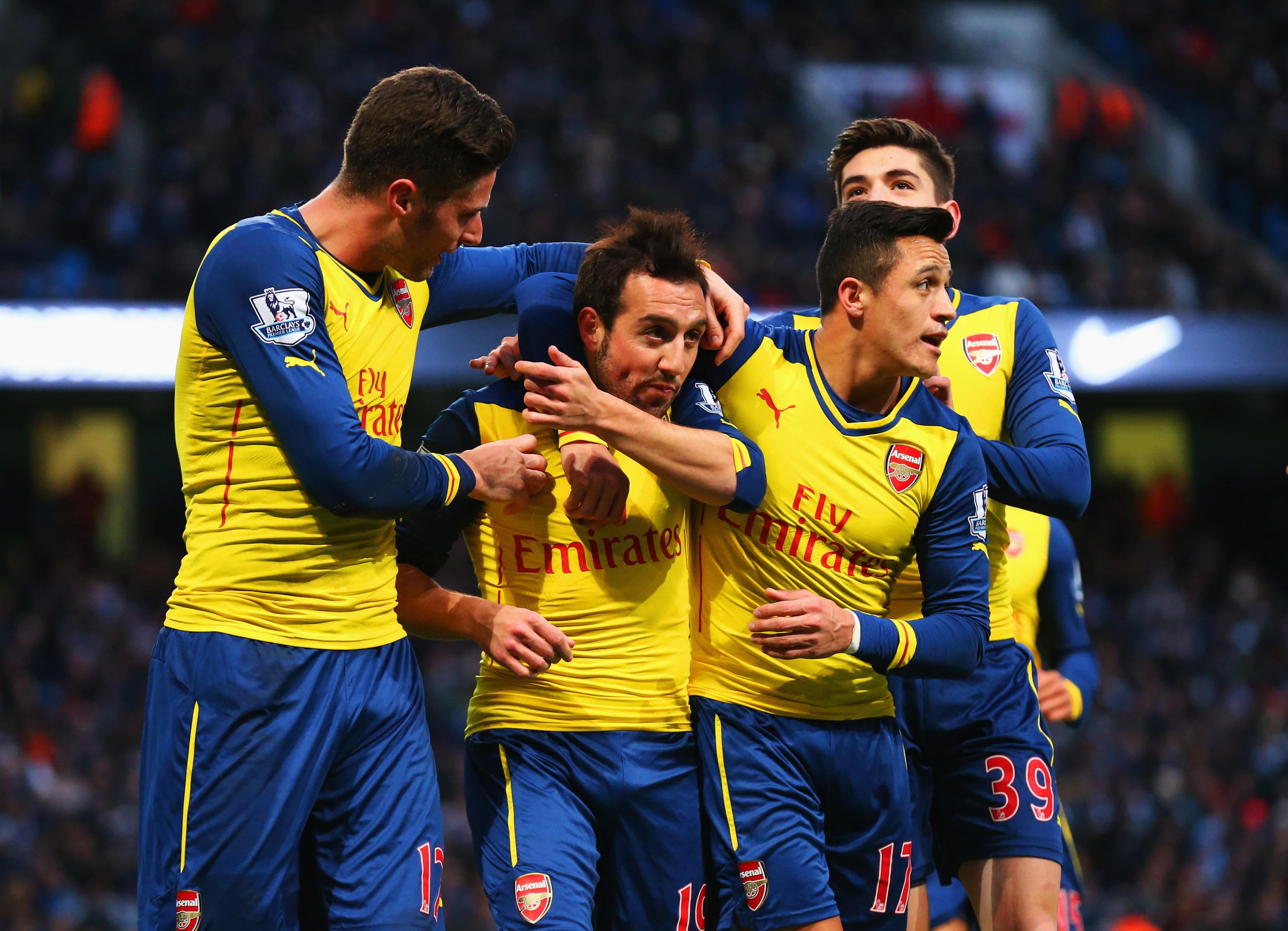 MANCHESTER, ENGLAND - JANUARY 18: Santi Cazorla of Arsenal (2L) celebrates with team mates